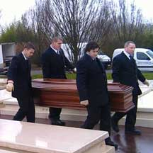 Cemetery workers and a coffin